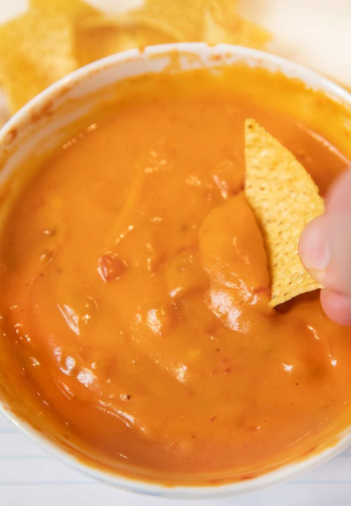 Chip dipping into Microwave Queso